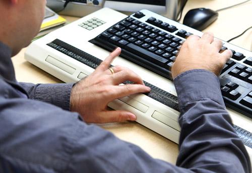 Hombre ciego usa línea braille con teclado de computadora de escritorio
