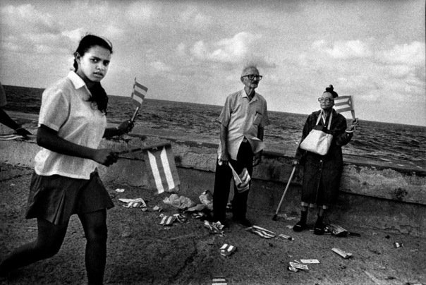 personas con banderas cubanas, dos ancianos y una adolescente