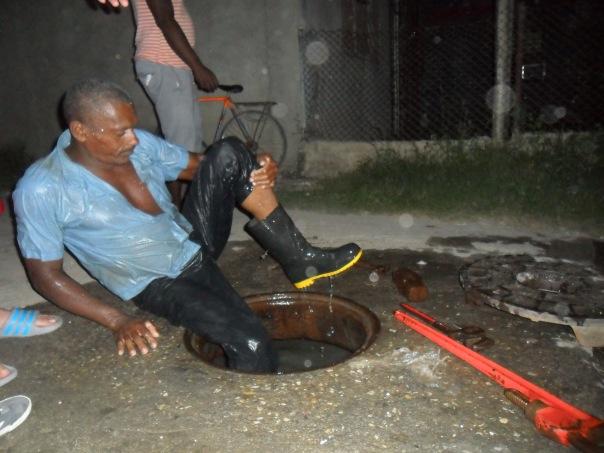 Trabajador de Acueductos y Alcantarillados trabajando de noche sin todos los medios de protección